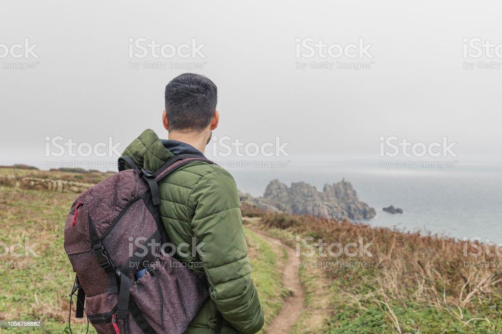 Man out walking along the Cornish coast at Penn Vounder stock photo