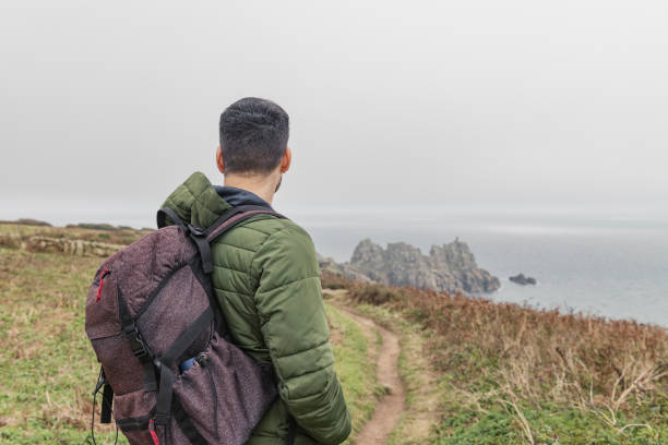 man out walking along the cornish coast at penn vounder - cornwall stock photos and pictures