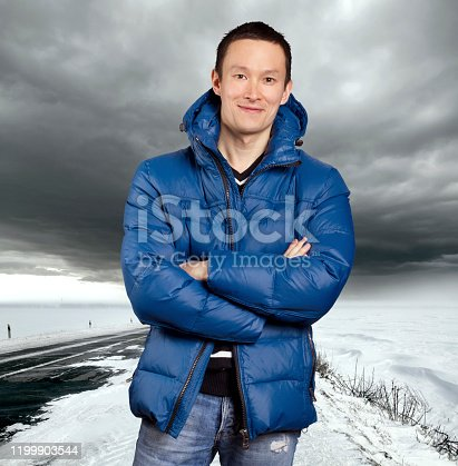 Man outdoors. Asian man stand on snow road in winter. Beautiful stormy sky with clouds and snow road