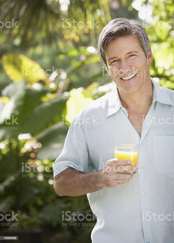 Mann von Bäumen holding Orangensaft Lizenzfreies stock-foto