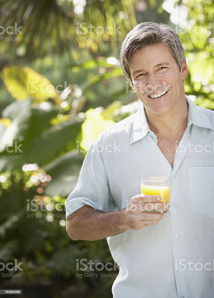 Man outdoors by trees holding orange juice stock photo