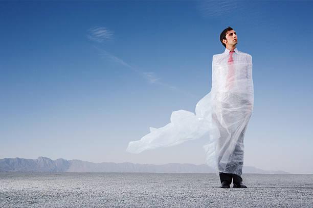 Man outdoors ensnared in a sheer sheet stock photo