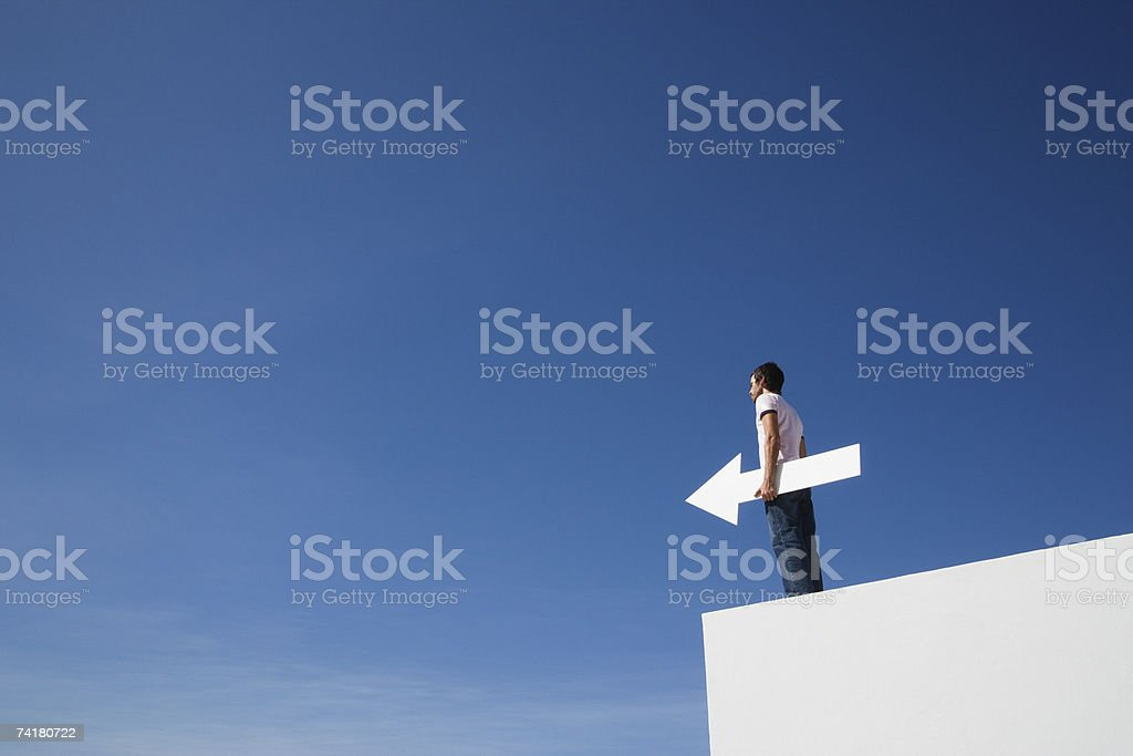 Man outdoors on wall with blank arrow royalty-free stock photo