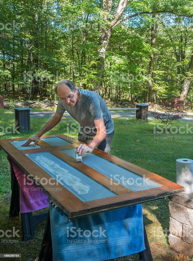 man outdoors painting door stock photo