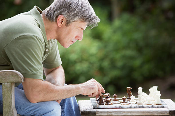 Man outdoors playing chess stock photo