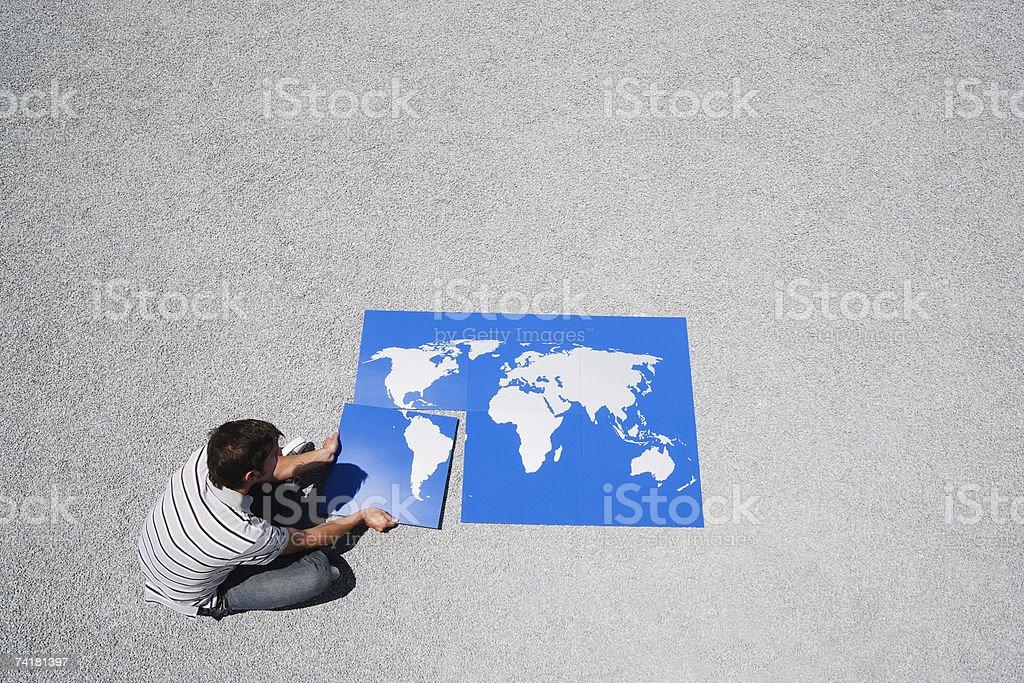 Homem ao ar livre com o mapa do mundo'puzzle' foto de stock royalty-free