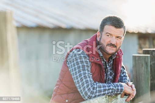 istock Man outside barn leaning on wooden fence 637179466
