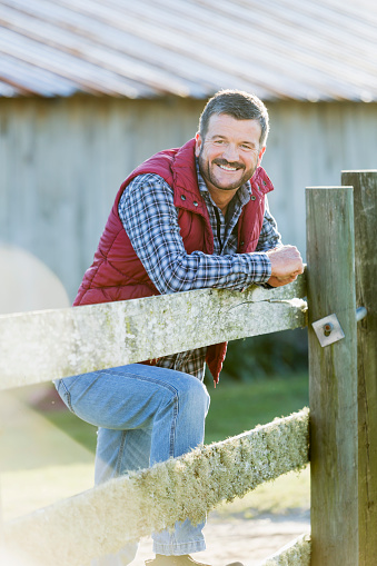 istock Man outside barn leaning on wooden fence 637289928