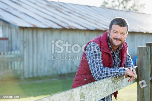 istock Man outside barn leaning on wooden fence 638481158