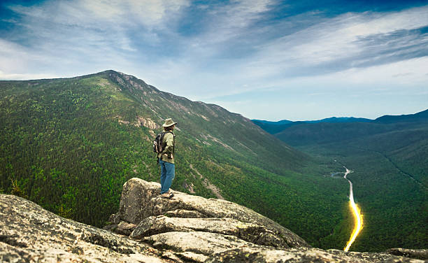 Man overlooking Crawford Notch from cliff in New Hampshire stock photo