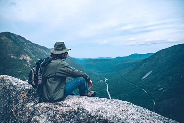 Man overlooking Crawford Notch in New Hampshire Male hiker sitting on the cliff of Mt Willard overlooking Crawford Notch in New Hampshire on the calm spring evening. appalachia stock pictures, royalty-free photos & images