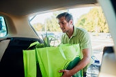 Man putting reusable shopping bags with groceries into the car trunk.