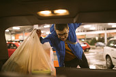 Man packing groceries from supermarket in car trunk
