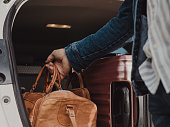 Man packing in his luggage suitcase in his car ready for road trip\nPhoto taken outdoors of man with bags by his Station wagon