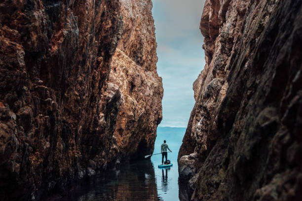 Man paddleboarding out of the narrow canyon stock photo