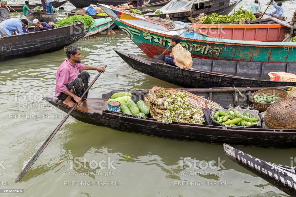 Barisal, Bangladesh - July 12, 2016: Man paddling a boat full of vegetables and water lilies at the floating vegetable market stock photo