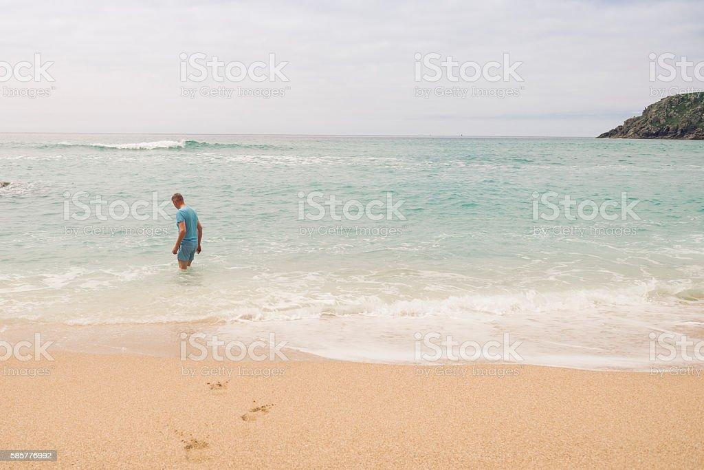 Man paddling at Pedn Vounder Beach, Cornwall. stock photo