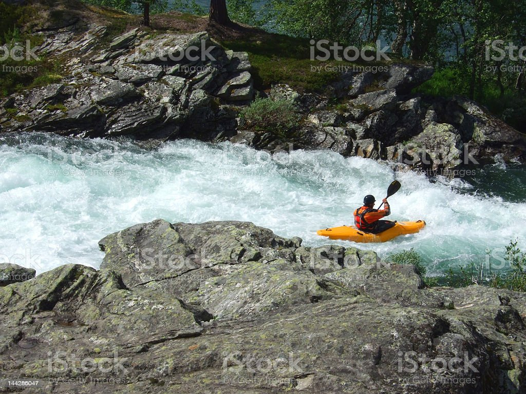 A man paddling in a canoe around the rocks stock photo