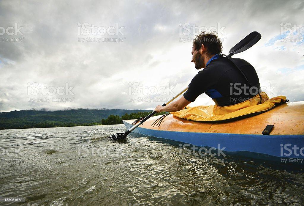 Man paddling in wooden kayak stock photo
