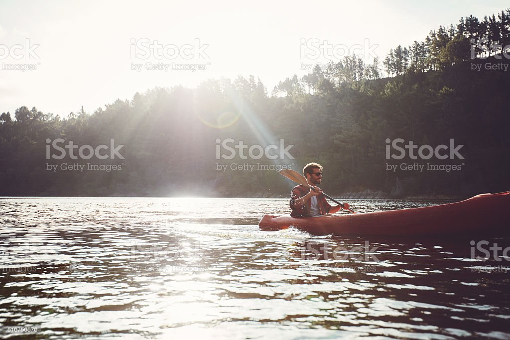 Man paddling kayak on a summer day Young man canoeing in a lake. Man paddling kayak on a summer day. Active Lifestyle Stock Photo