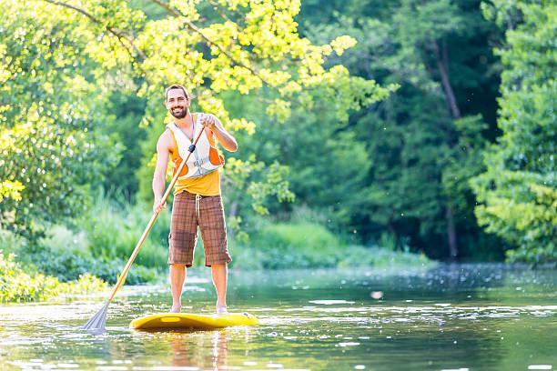man paddling on sup in river - stehpaddeln stock-fotos und bilder