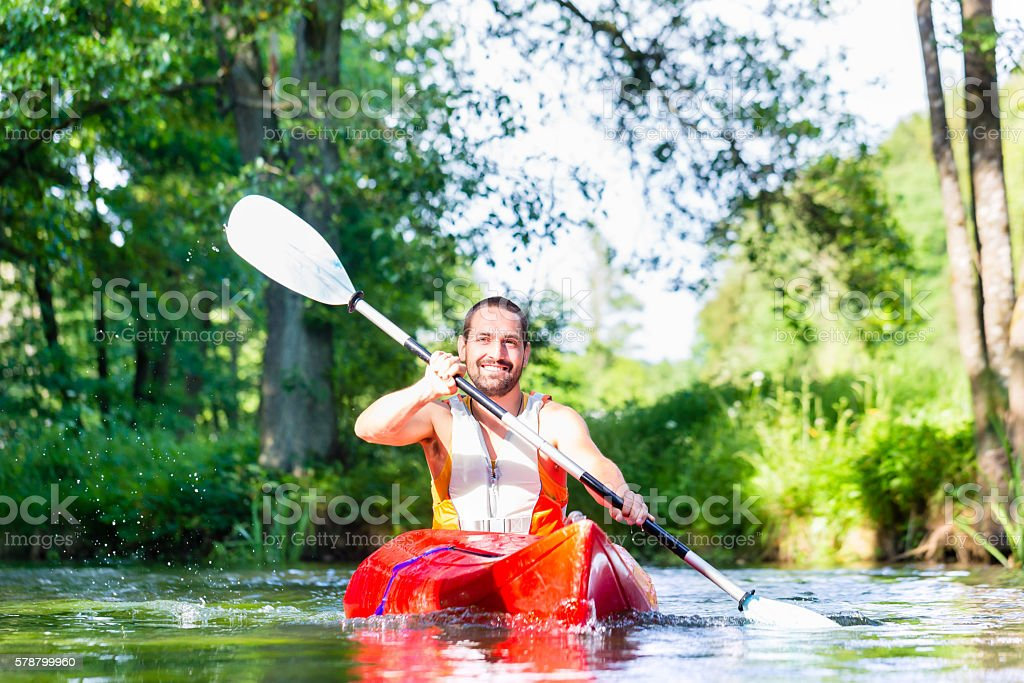 Man paddling with canoe on forest river stock photo