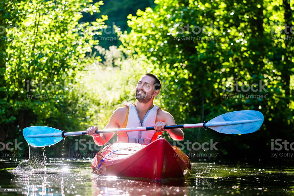 Man paddling with kayak on forest river for water sport stock photo