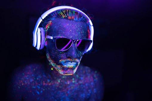 Man with glowing makeup in black light. Man with neon makeup powder on face. Man painted in fluorescent UV colors, with sunglasses and headset.