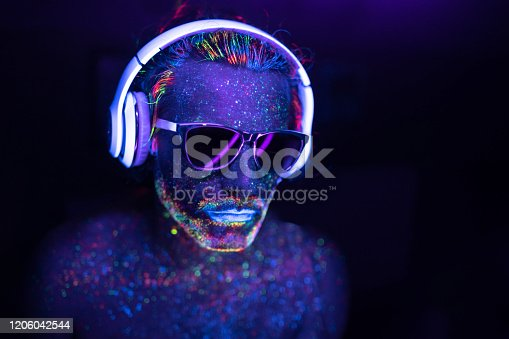 istock Man painted in fluorescent UV colors with sunglasses and headset 1206042544