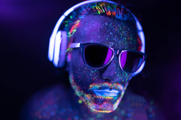 Man painted in neon colors with sunglasses and headset stock photo
