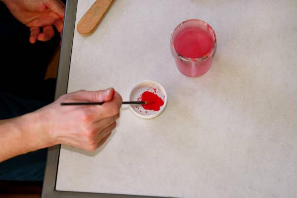 O pintor do homem está misturando cores antes de pintar no estúdio da pintura da arte. Artista em seu pincel da terra arrendada da mão pinturas de óleo misturadas da cor para a pintura na paleta, equipamento artístico, close up. Conceito da faculdade  - foto de acervo