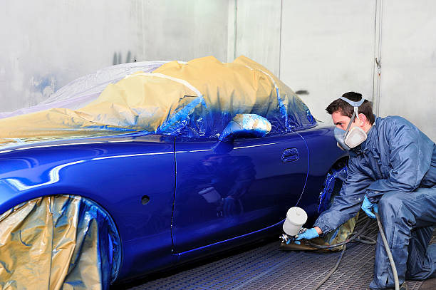 man painting a car. - auto body repair stock photos and pictures