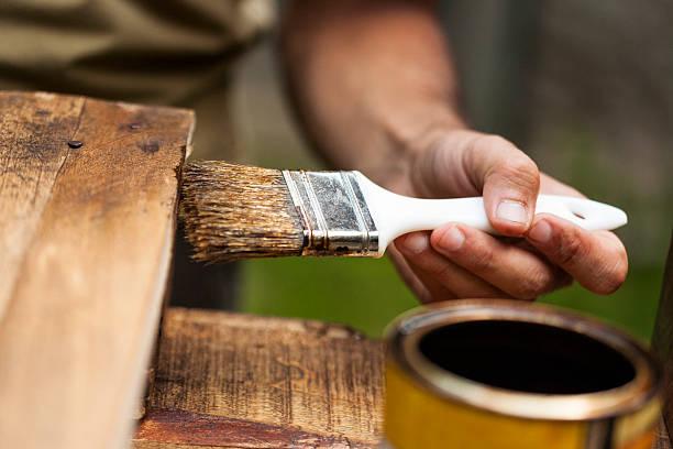 Homem pintando um deque de madeira ao ar livre - foto de acervo