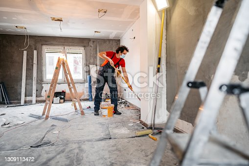Young man painting apartment walls and renovating apartment. He is wearing protective face mask.