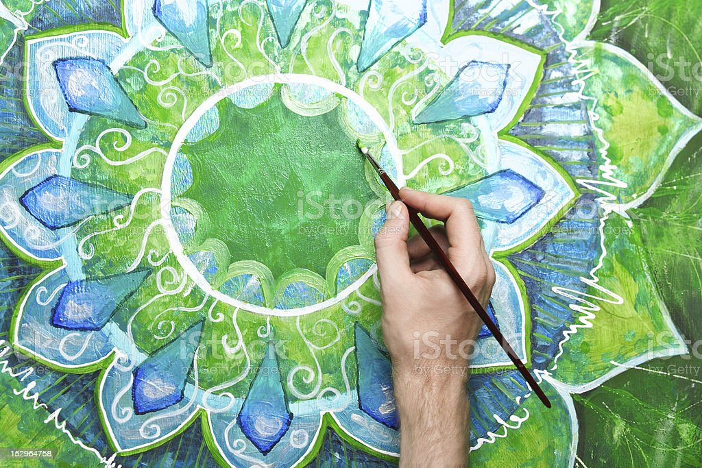 man painting bright green picture with circle pattern stock photo