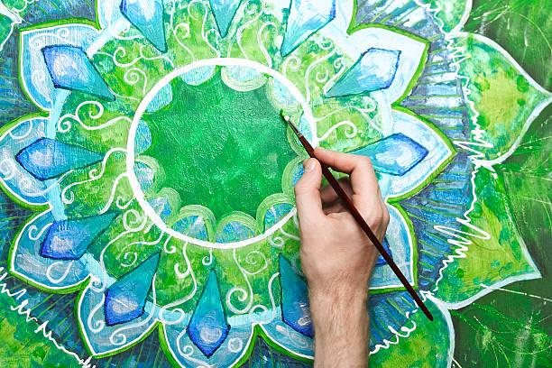 man painting bright green picture with circle pattern - mandala bildbanksfoton och bilder