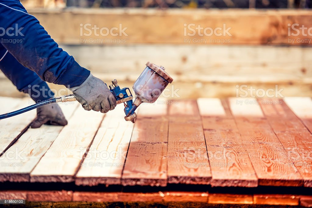 Man painting brown timber, renovating exterior wooden fence. stock photo