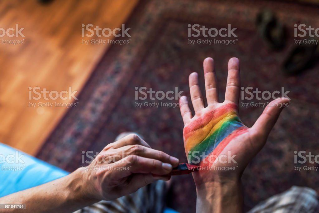 Man painting colored flag on hand stock photo
