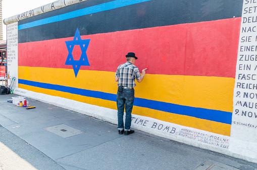 Man painting german flag on Berlin Wall.