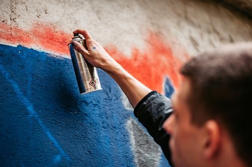 Man painting graffiti on wall