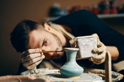 Man painting handmade pottery at ceramic workshop