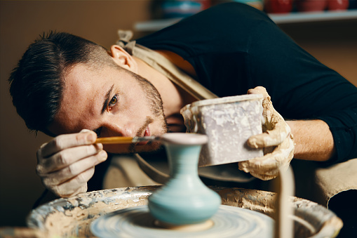 Man painting handmade pottery at ceramic workshop