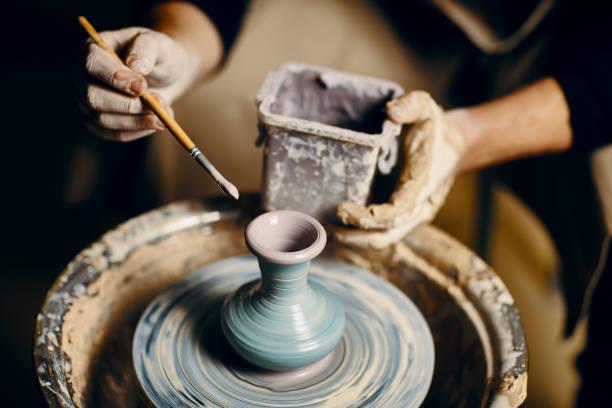 Mann malte handgemachte Keramik in der Keramikwerkstatt – Foto