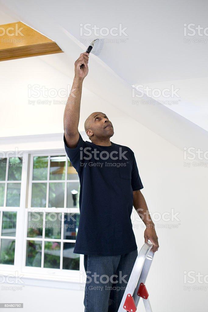 Uomo dipinto il suo soggiorno parete foto stock royalty-free