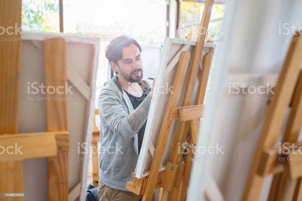 Pintura en una clase de arte del hombre - foto de stock