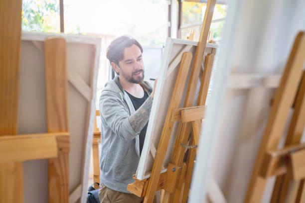 pintura en una clase de arte del hombre - clase de arte fotografías e imágenes de stock