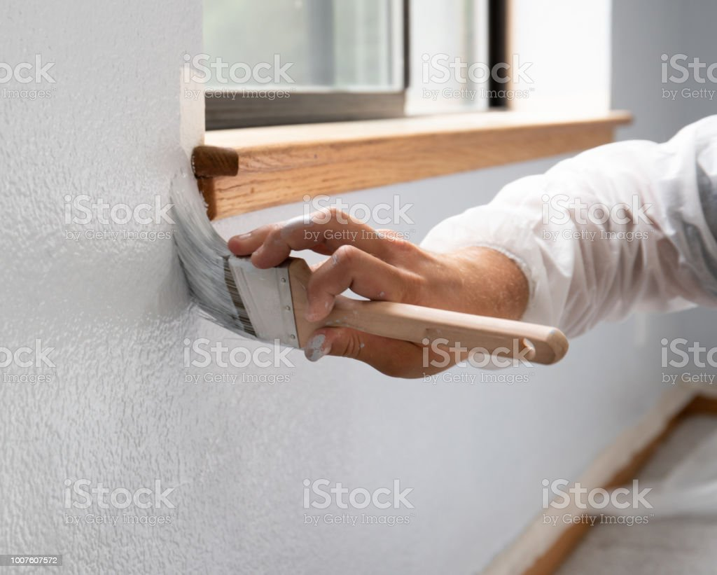 Man painting interior of home by window stock photo