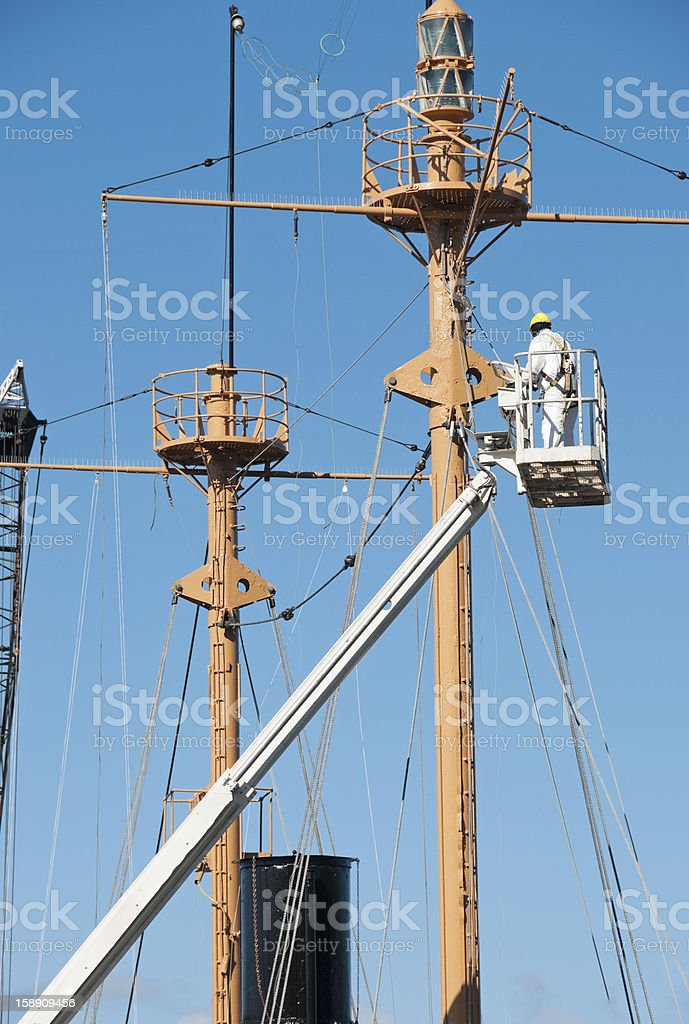 Man painting mast of lightship in dry dock royalty-free stock photo