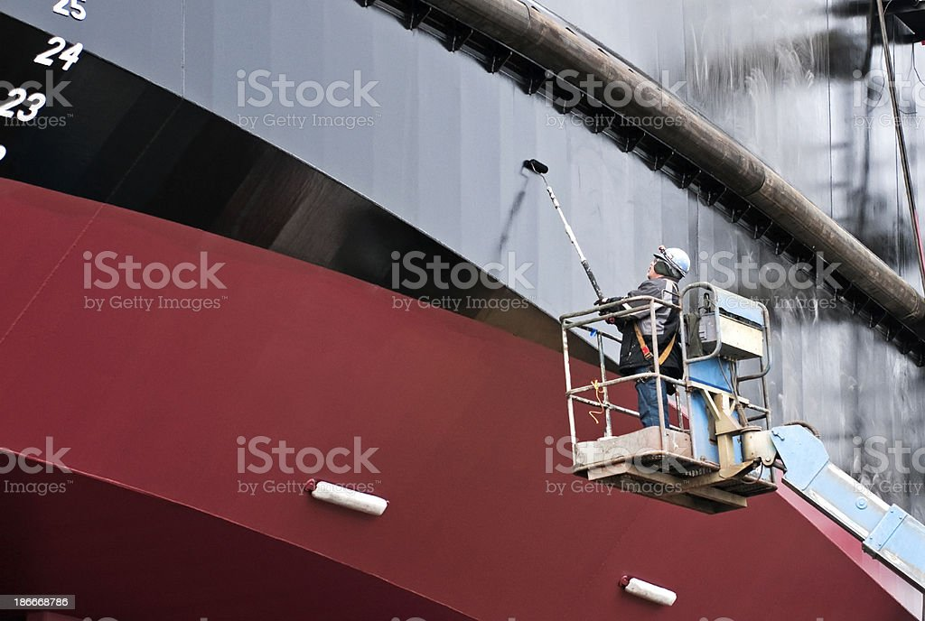 Man painting ship's hull with roller at dry dock stock photo