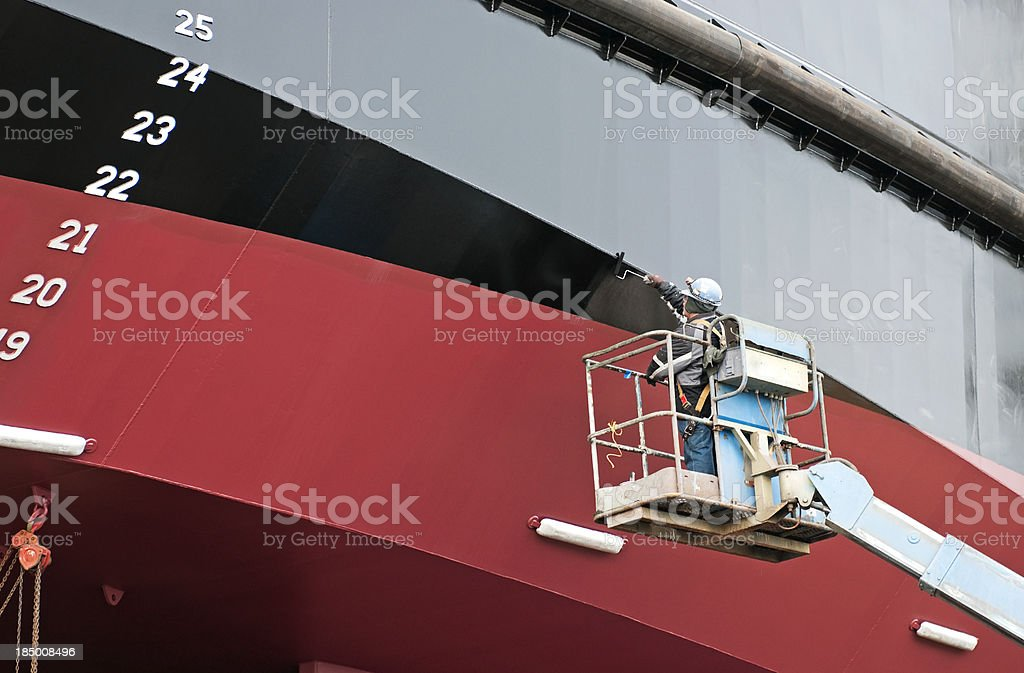 Man painting ship's hull with roller stock photo